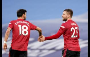Manchester United's Luke Shaw celebrates with Bruno Fernandes (left) after scoring his side's second goal during the English Premier League match against Manchester City at the Etihad Stadium in Manchester yesterday.