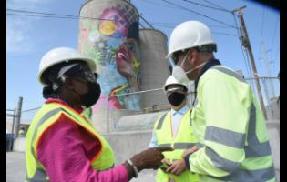 Minister of Culture, Gender, Entertainment and Sport, Olivia Grange (left), speaks with Mexico's Ambassador to Jamaica,  Juan José González Mijares (centre), and General Manager of Caribbean Cement Company Limited, Yago Castro Izaguirre, during a recent visit to Caribbean Cement's Rockfort complex in east Kingston to view a mural painted on a silo. The artwork adds to the ongoing 'Jamaica Creative: Paint Up Yuh Creative Space' mural project, which commenced in December 2019.
